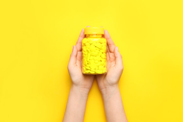 Female hands with pills in bottle on color background