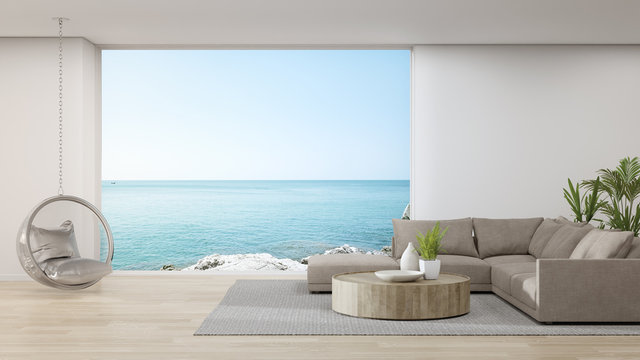 Sofa on wooden floor of large living room in modern house or luxury hotel. Minimal home interior 3d rendering with sky and sea view.