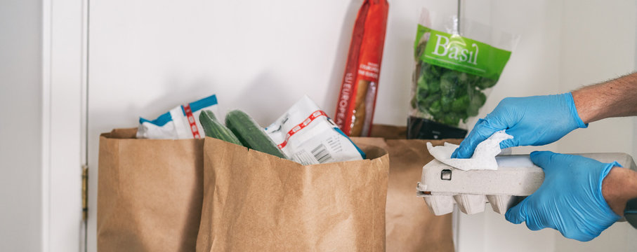 Cleaning groceries with disinfecting wipes as coronavirus prevention. Man wiping down grocery packages after receiving home delivery wearing gloves to wipe the surfaces clean. Cleaning of COVID-19.