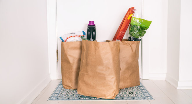 Grocery online delivery receiving grocery bags at home entrance door outside doorstep hallway contactless reception of food deliveries during quarantine COVID-19 Coronavirus.