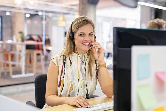 Smiling call center operator at desk