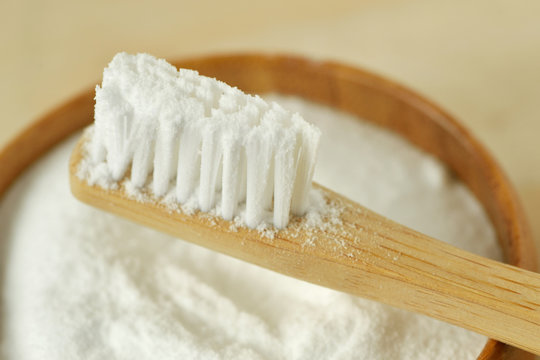 Close-up of baking soda in a bowl with a wooden toothbrush - Teeth whitening