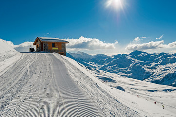 Wall Mural - Panoramic view across snow covered slope on alpine mountain with small hut