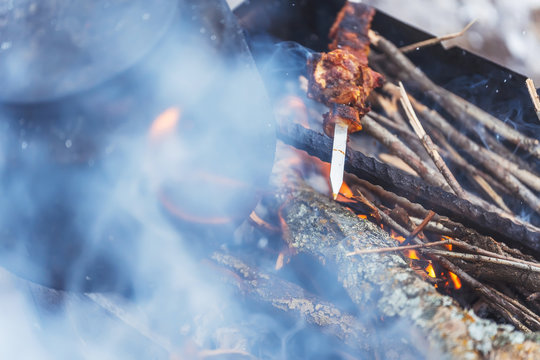 Camp smoky kettle on the grill with barbecue. One stick the skewer with the meat on the grill. Barbecue in the smoke on a winter picnic