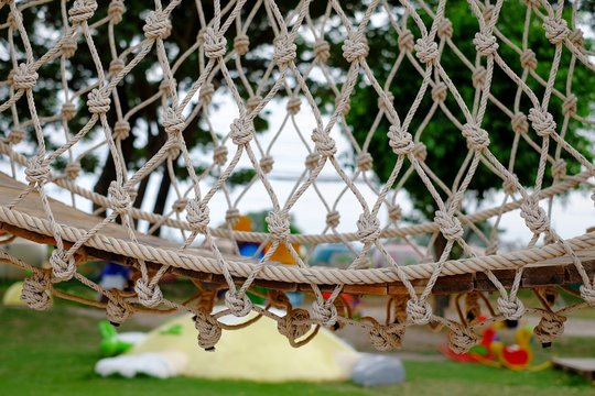 A closeup picture of a rope and wooden bridge from an obstacle course in a playground.