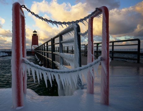 Frozen Pier Leading Towards Lighthouse Over River Against Cloudy Sky
