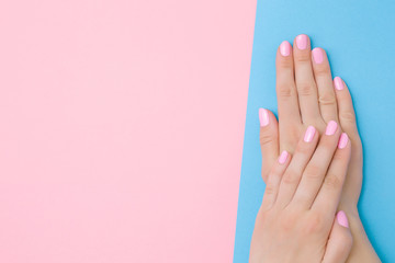 Foto op Textielframe Spa Beautiful groomed woman hands with light pink nails on pastel blue table side. Two colors background. Closeup. Manicure, pedicure beauty salon concept. Empty place for text or logo. Top down view.