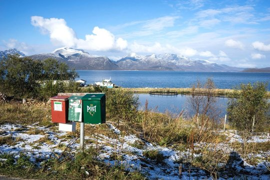 Mail Box On Grassy Field By Lake Against Cloudy Sky During Winter