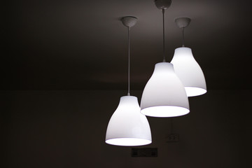 Three white electric light lamps  hanging on ceiling interior background Wall mural