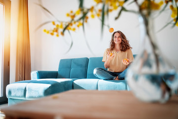 Wall Murals Relaxation Charming beautiful young girl with curly hair and a happy smile juggles tangerines while sitting on a blue sofa in her living room at home, having fun staying at home