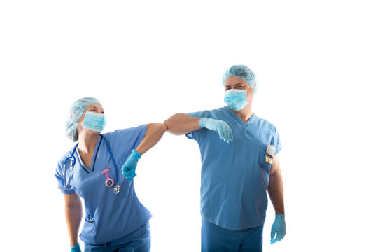 nurses in scrubs elbow bump instead of shaking hands during COVID-19 pandemic