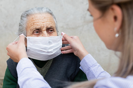 Nurse putting on mask on elderly woman