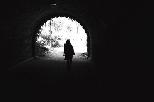 Rear View Of Silhouette Woman In Tunnel