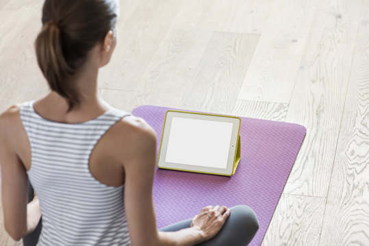 Young woman practicing yoga at home, online video training, girl doing exercises and meditate. Yoga, meditation, relaxation, healthy lifestyle, pilates, online training concept, blank empty monitor