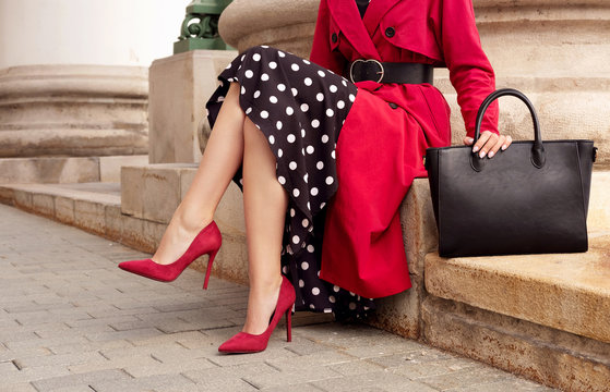 Fashionable woman in red coat, heels, black bag. Outdoor fall and spring outfit