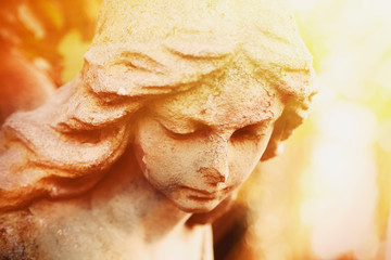 Wall Mural - Fragment of ancient stone statue of very beautiful angel in sunlight.
