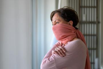 Thoughtful woman wearing a face guard