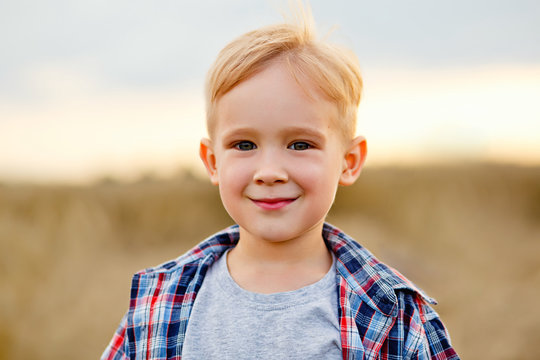 Portrait of a happy and beautiful little boy with curly blond hair and a white shirt, looking forward standing with a bucket in his hand in the field of yellow wheat. Happy childhood. Positive emotion