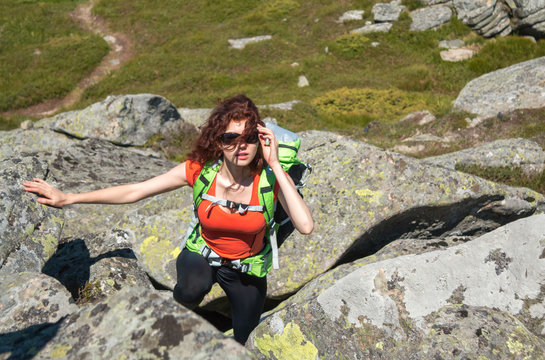 Caucasian girl in sunglass with red hair climbing on stones in mountain
