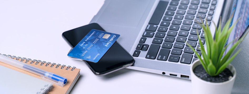 Online paying shopping, electronic payment with credit card, smart phone concept, laptop over white table background with shop cart trolley, close up.