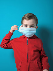 Child putting on a surgical protective mask
