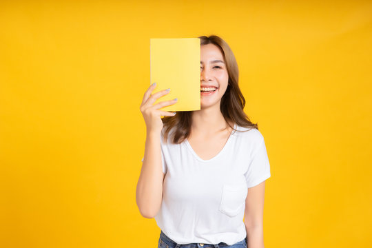 Portrait young happy asian woman book covering your eye reading education studying learning knowledge smiling positive emotion in white t-shirt, Yellow background isolated studio shot and copy space.