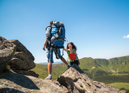 Close-up of loving couple hikers climbing up on the peak of mountain. Climbing, Helps and Team work concept