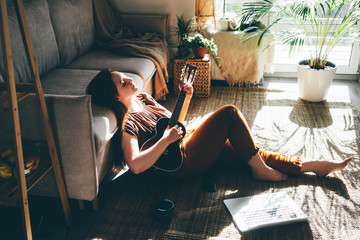 Woman playing music with ukulele at home, relaxation and recreation concept. Fotobehang