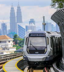Foto op Textielframe Kuala Lumpur Malaysia Mass Rapid Transit (MRT) train with a background of Kuala Lumpur cityscape. People commute with MRT as transportation to work, school, travel, and shopping.