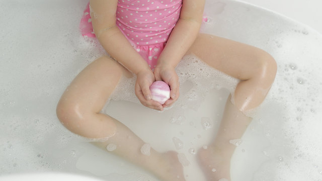 Hands of girl puts bath bomb to water. Ball of bath salt dissolves in water
