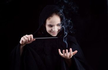 A girl in a witch's cloak with a magic wand in his hand conjures magic. Halloween outfit Wall mural