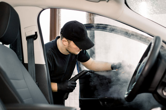 Auto cleaning service and detailing concept. Handsome Caucasian man in black uniform cleaning interior of the car with hot steam cleaner. Selective focus.