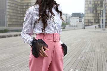 Faceless brunette female figure in white blouse and pink pants on street in Paris. Street fashion Wall mural