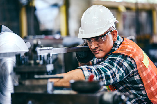 Male engineer metalworker industrial experienced operator technician worker in safety hard helmet working on lathe machine, professional man in industry technology manufacturing factory workshop