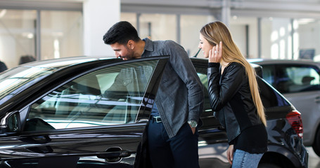 Young couple choosing new car for buying in dealership shop Fotomurales