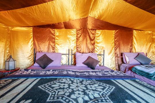 Beds inside elegant tent set on Sahara desert, Morocco