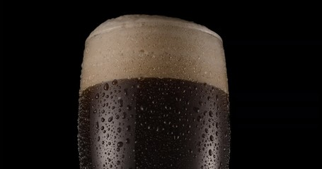 Wall Mural - Glass of black beer on a black background. Beer sways in the glass, bubbles and foam rise. Glass of beer rotates slowly clockwise.