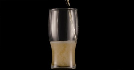 Wall Mural - Glass of light beer on a black background. A jet slowly fills the glass with beer, causing abundant bubbles and foam.