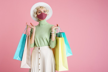 Spring shopping during quarantine conception: fashionable woman wearing protective mask posing with colorful paper bags. Pink background. Copy, empty space for text Fotobehang