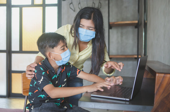 Lockdown and school closures. Mother helping her child with face mask studying online classes at home. Quarantine, self-isolation, online education concept, home schooler during COVID-19 pandemic