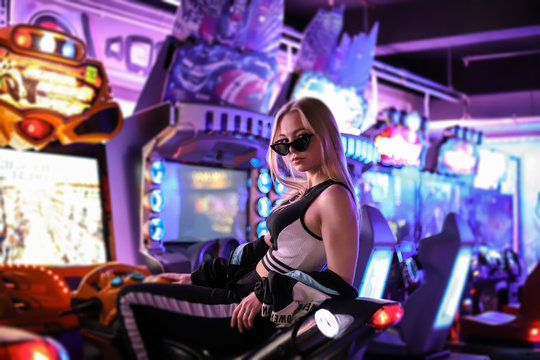 A beautiful sexy blonde girl in dark glasses poses on a motorcycle racing simulator under neon lights. Girl under the neon lights. Video games, virtual reality, slot machines. Girl gamer.