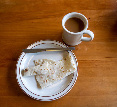 Top down view of a plate with traditional scandinavian potato lefse and a butter knife, and a cup of coffee on a wooden table.