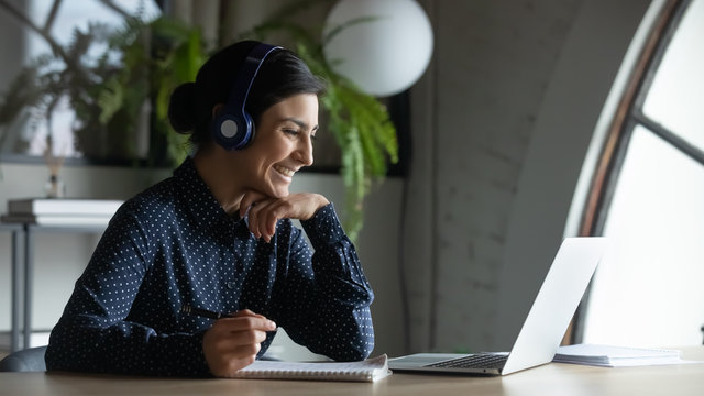 Smiling Indian female employee in wireless earphones talk on video call, have web conference with colleagues, happy ethnic woman worker in headset watch webinar on modern laptop at home