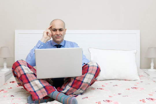 Man working with a laptop on a bed dressed in a shirt and tie and thinking expression