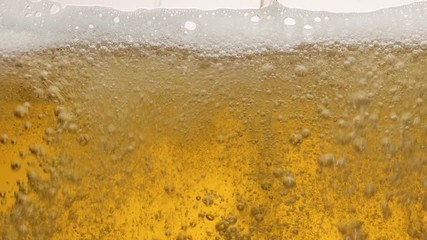 Wall Mural - Close-up of the contents of a glass of beer. Beer is slowly poured into a glass, causing a lot of bubbles, waves and foam.