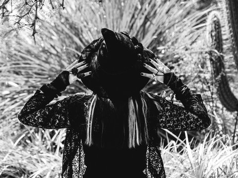 Beautiful young gothic and witch woman from back with hands with black nails and accessories over witchy hat in forest, in black and white