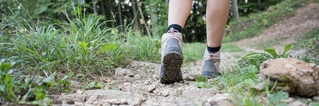 Female legs in hiking boots on forest trail