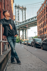 Wall Mural - Young man standing on the Washington street, in Brooklyn with a Manhattan bridge in the background.