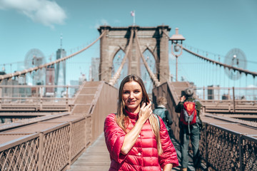 Fototapete - Young beautiful girl walking down the  Brooklyn Bridge with a magical Manhattan island view.