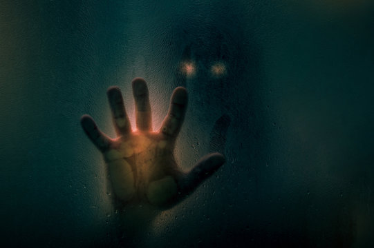 Horror scene of a man with bloody hand against wet shower glass. Toned image. Horror concept